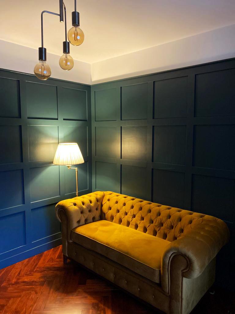 Musztardowa sofa dwuosobowa Chesterfield Grand w pokoju w stylu retro