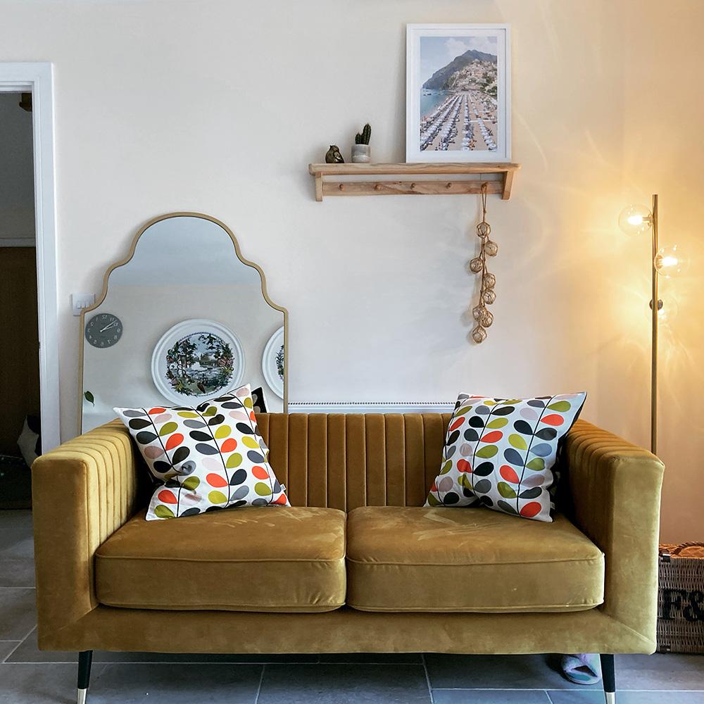 Musztardowa sofa w pokoju ze złotymi dodatkami